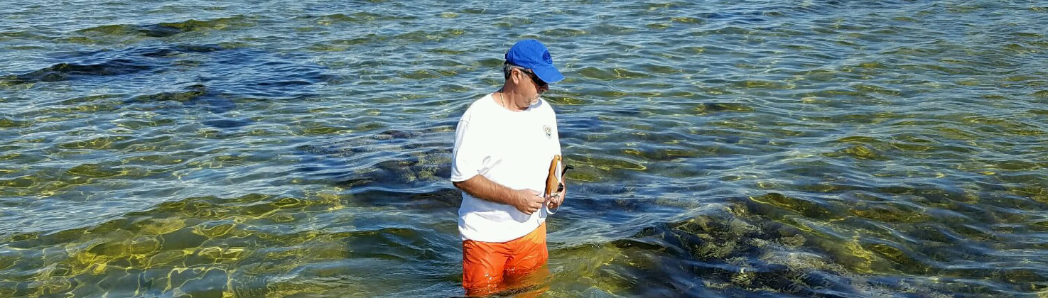 photo of a water watch volunteer wading while collecting a sample