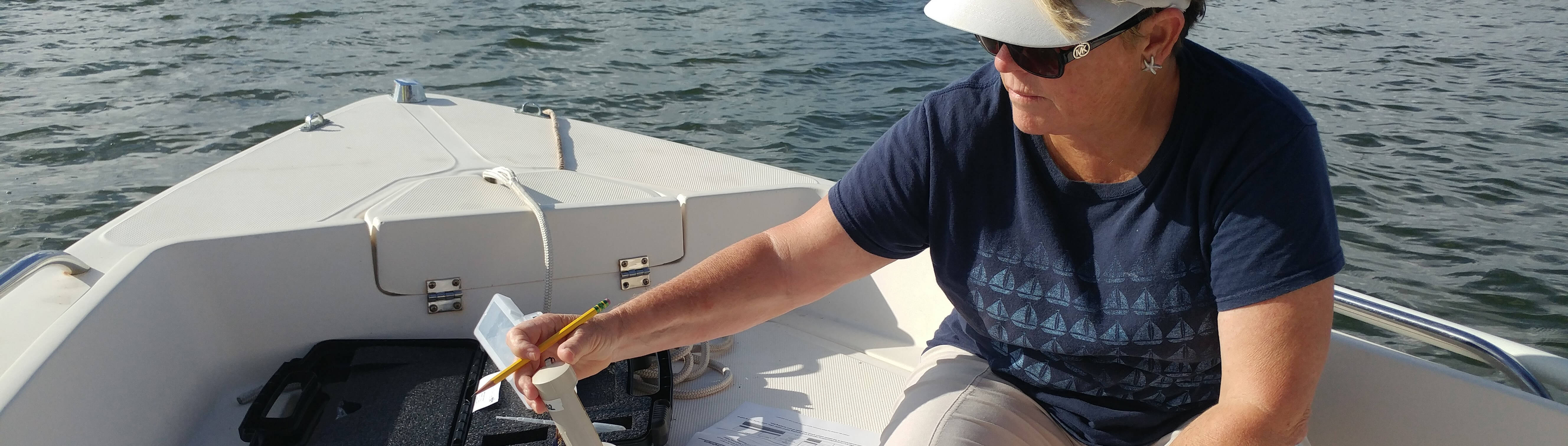 photo of a water watch volunteer collecting a sample in a boat